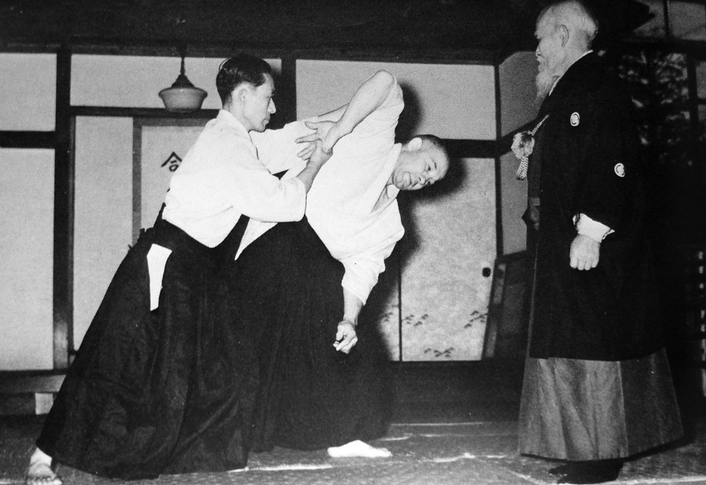 Ueshiba Kisshomaru and André Nocquet practicing in front of O Sensei